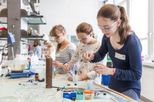 Junge Maedchen bedienen Laborgeraete